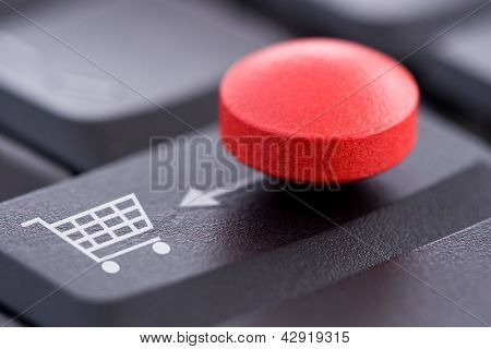 Red Pill And Shopping Cart On Computer Keyboard