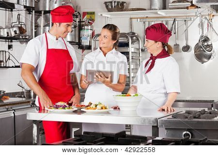 Female chef with colleagues looking for recipe on a tablet computer while cooking at kitchen
