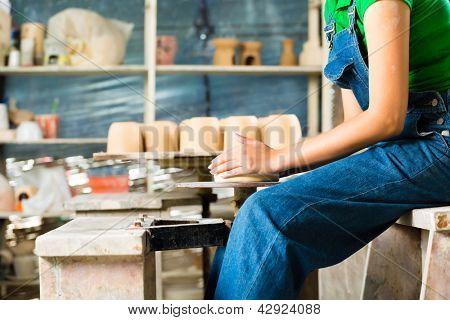 Weibliche Potter erstellen eine Schüssel auf einer Töpferscheibe