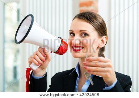 Junge Makler ist mit Schlüsseln im Appartement, sie macht Werbung mit einem Megaphon