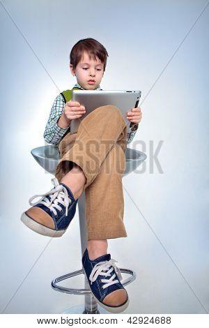 Menino bonito com um tablet pc