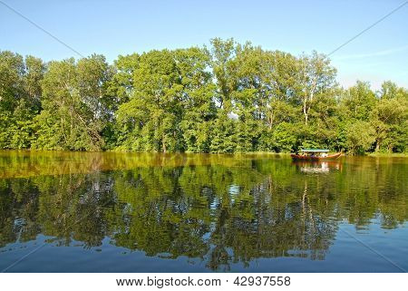 Touristic boat on the lake. Summer time. Royal park in Wilanow near Warsaw. People faces unrecognized.