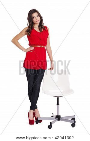 Fashionable woman standing next to a chair