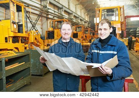 adult experienced industrial workers examining technical drawing during heavy industry machinery assembling on production manufacturing line