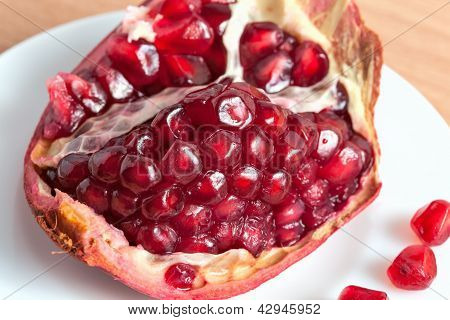 The cut pomegranate and grains on a plate