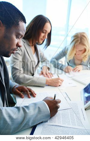 Confident businessman signing papers with his two employees working on background