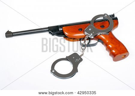 Airgun with handcuffs isolated over white.