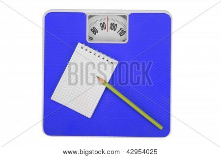 Scales and notebook with a pencil.