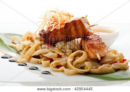 Udon (thick wheat noodles) with Skewered Salmon and Vegetables. Garnished with Banana Leaves and Sauce