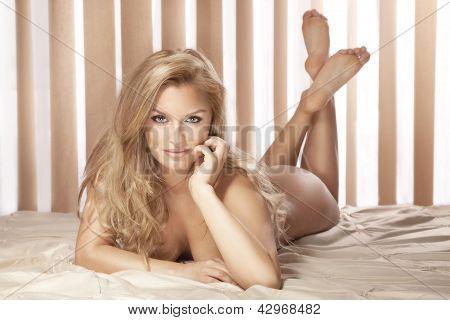 sexy blonde Frau liegt nackt auf dem Bett, Blick in die Kamera