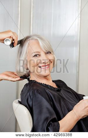 Portrait of happy senior woman getting hair styled in salon