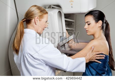 Mature female doctor assisting young patient undergoing mammogram