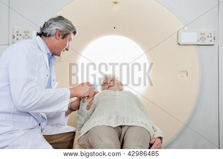 Mature male radiologist comforting an elderly senior woman before CT scan