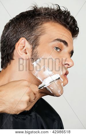 Closeup of mature man shaving his face isolated over white background