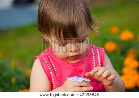 little girl  holding flower outdoors