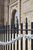 image of cameos  - Vertical take of the Gateway of India its black and silver painted railings with a defocused cameo view of the Taj Hotel from an angled view of an archway