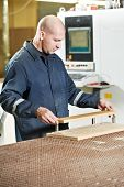 worker with wood furniture detail at wardrobe manufacturing production