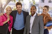 foto of fellowship  - Portrait of happy businessteam standing hugging outdoors - JPG