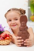 Happy easter girl with chocolate bunny and dyed eggs - closeup