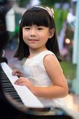 picture of white gown  - Happy little Asian girl is playing piano