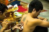 NAKHON CHAI, THAILAND - MAR 1: Unidentified monk makes traditional Yantra tattooing on Mar 1, 2012 i
