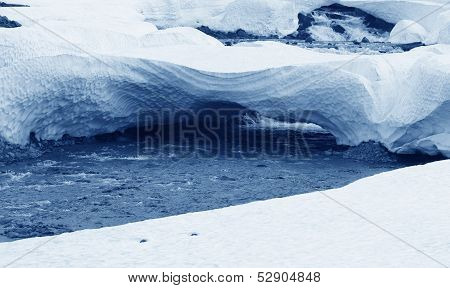 Iceland. West Fiords. River, Snow And Ice Blocks.