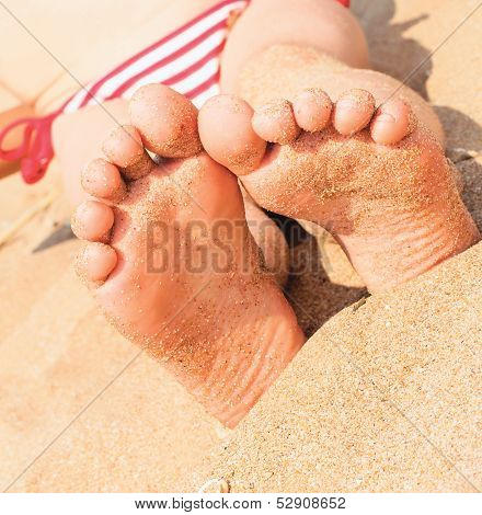 Child's Foot Is Close To The Sandy Beach