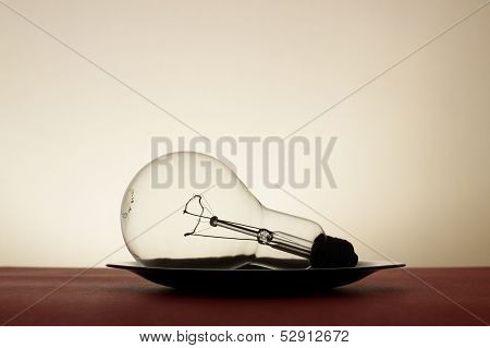 Big Light Bulb In Black Plate On Red Tablecloth