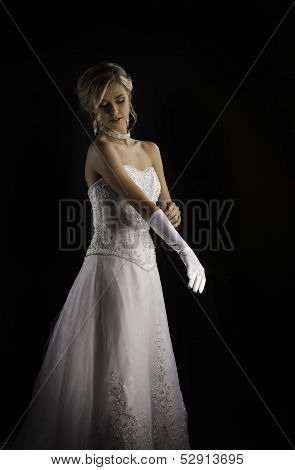 Beautiful blonde bride putting on long white gloves