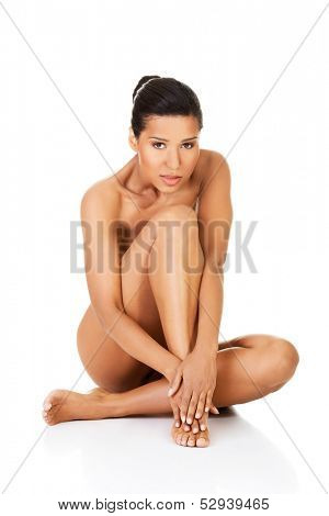 Beautiful naked young woman sitting. She is covering her nudity by her leg and hands. Isolated on white.