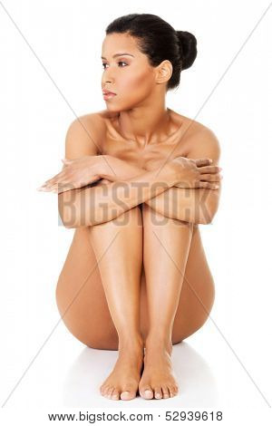 Beautiful and naked women sitting and covering her nudity by her legs and arms. Front view. She's looking into a right side. isolated on white.