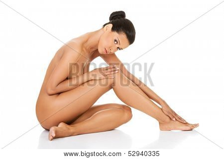 Beautiful and naked woman sitting. Side view. Legs half-straight. Isolated on white.