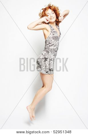 Young charming female in dress jumping over white background