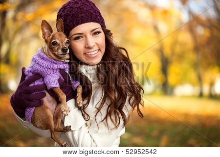 Young woman holding her miniature pincher puppy after playing in the park
