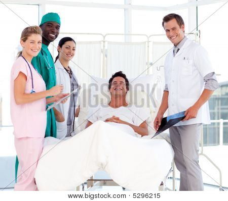 Doctors Attending To A Patient Smiling At The Camera