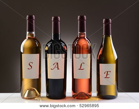 Four Wine Bottles with their labels spelling out the word SALE on a light to dark gray background. Wines include: Cabernet Sauvignon, Chardonnay, Sauvignon Blanc, and White Zinfandel.