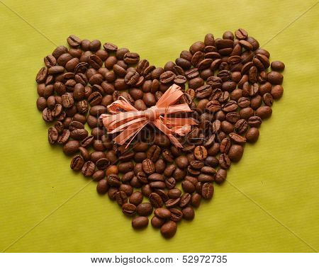 Photo of coffee beans in a shape of heart with bow on green background