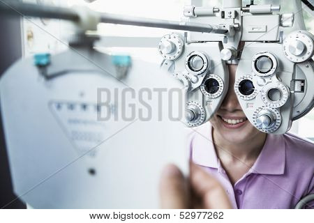 Close-up of optometrist doing eye exam on young woman
