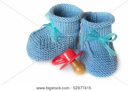 pair of blue knit children's bootees and baby's dummy on a white background
