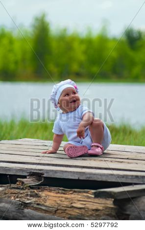 Little Child Laughs Loudly On The Timber Flooring Near River
