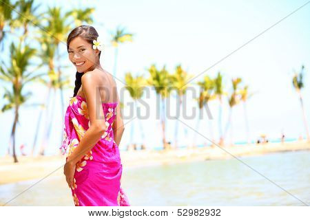 Beach travel - woman smiling happy on Hawaii. Girl in sarong cheerful on sunny hawaiian palm tree beach on holiday resort vacation. Big Island, Hawaii, USA. Multicultural Asian Caucasian female model.