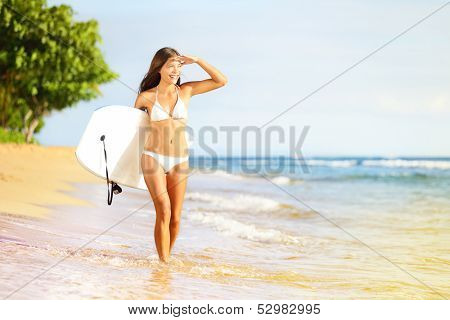 Surfboard woman walking in beach water holding bodyboard. Beautiful surfer girl in white bikini going bodyboarding looking out over the sea enjoying sun. Mixed race Asian Caucasian, Maui, Hawaii, USA.