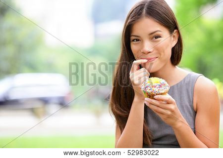 Cupcakes - woman eating cupcake in New York, Central Park, Manhattan. Business woman eating unhealthy food snack in lunch break smiling happy. Beautiful casual businesswoman in New York City, USA.