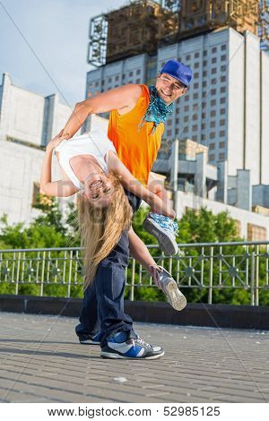 Young beautiful couple doing acrobatic stunts in the street dance