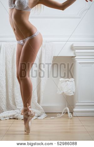 Beautiful female body standing on tiptoe in lacy lingerie and pointe in studio