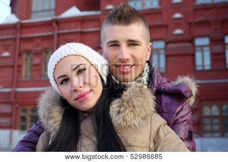 Beautiful man and woman embrace near red building at winter day.