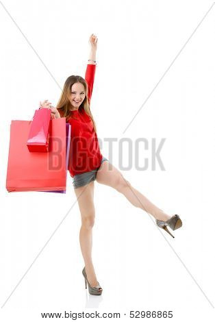 Beautiful excited teen girl with shopping bags. Full length portrait of young fashion woman.