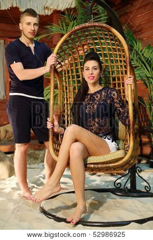 Man stands near wicker hanging chair with young woman next to beach house.