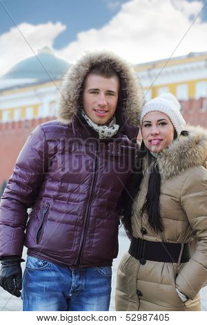 Young man and woman in warm clothes stand at street at winter day.