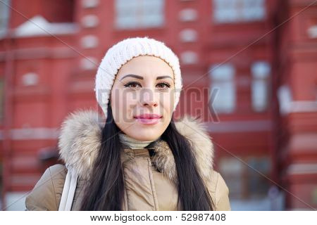 Beautiful woman in white hat stamds near red building at winter day.